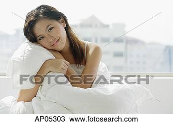 Banco de Imagem - jovem, mulher,  sentando, cama,  abraçar, travesseiro.  fotosearch - busca  de fotos, imagens  e clipart