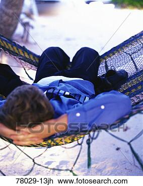 Stock Photo - young businessman lying in hammock on beach, belize. fotosearch - search stock photos, pictures, images, and photo clipart