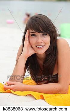 Banco de Imagem - jovem, mulher,  mentindo, praia,  toalha. fotosearch  - busca de fotos,  imagens e clipart