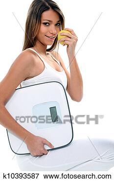 Foto - jovem, magra,  mulher, maçã,  banheiro, escala.  fotosearch - busca  de fotos, imagens  e clipart