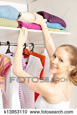 Arquivo de Fotografias - mulher, chooses,  roupas, guarda-roupa,  armário, lar.  fotosearch - busca  de fotos, imagens  e clipart