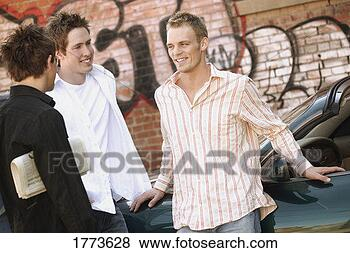 Stock Photo - group of guys  hanging out near  car. fotosearch  - search stock  photos, pictures,  wall murals, images,  and photo clipart