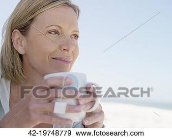 Arquivo Fotográficos - mulher, praia,  copo, chá. fotosearch  - busca de fotos,  imagens e clipart