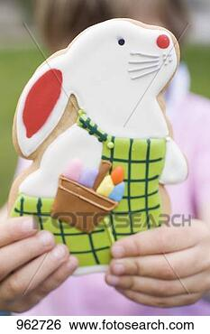Stock image child holding easter bunny biscuit fotosearch search