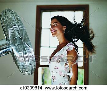 Banco de Imagem - mulher, ficar,  frente, elétrico,  ventilador. fotosearch  - busca de fotos,  imagens e clipart