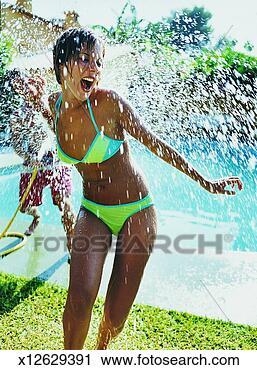 Arquivo de Fotografia - mulher, pulverizado,  água, mangueira.  fotosearch - busca  de fotos, imagens  e clipart