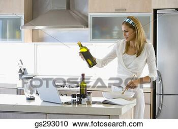 Arquivo de Fotografias - mulher, cozinhar,  laptop, cozinha.  fotosearch - busca  de fotos, imagens  e clipart