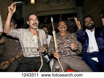 Stock Photography - a group of men  smoking shisha  pipes and cheering  musicians in a  cafe. fotosearch  - search stock  photos, pictures,  images, and photo  clipart