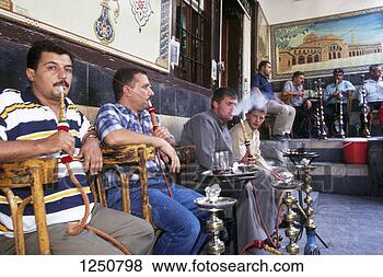 Stock Photo - men sitting outside  a cafe in the  old city smoking  hookahs. fotosearch  - search stock  photos, pictures,  images, and photo  clipart
