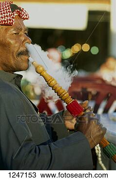 Stock Photo - a man smoking  a hookah, kuwait.  fotosearch - search  stock photos,  pictures, images,  and photo clipart