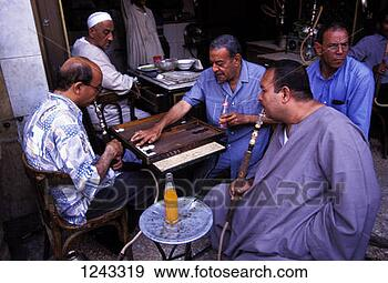 Stock Photograph - men playing backgammon  and smoking shishas  at a cafe in the  bab al. fotosearch  - search stock  photos, pictures,  images, and photo  clipart
