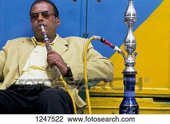Stock Photo - a middle-aged  man sitting smoking  a hookah in tripoli,  libya. fotosearch  - search stock  photos, pictures,  images, and photo  clipart