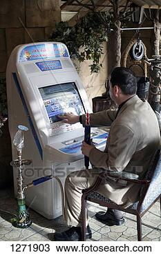 Stock Photo - emirati with a  shisha pipe playing  on an arcade machine,   dubai. fotosearch  - search stock  photos, pictures,  images, and photo  clipart