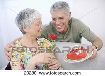 Arquivo de Fotografias - sênior, romancing,  mulher, valentine,  bolo, vermelho,  rosa. fotosearch  - busca de fotos,  imagens e clipart