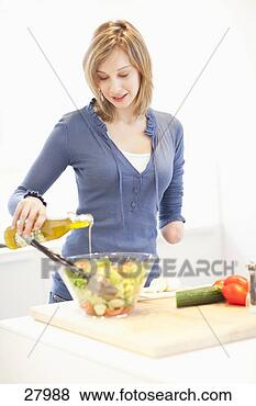 young woman with amputee arm making salad in kitchen 27988
