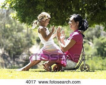 Foto - mãe, filha, sentando,  empurrão, scooter,  parque, menina,  mulher. fotosearch  - busca de fotos,  imagens e clipart