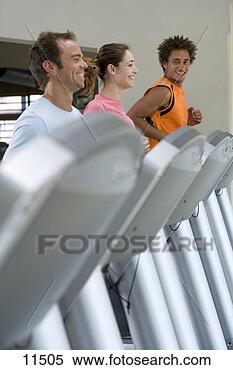 Stock Image - man on treadmill  smiling at man  and woman running  on treadmills  in gym. fotosearch  - search stock  photos, pictures,  images, and photo  clipart