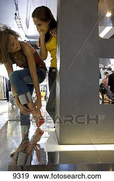 Stock Photograph of Two young women shopping in clothes store, one