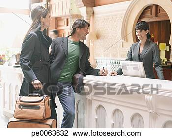 Stock Photo of Hotel receptionist checking couple in pe0063632 - Search Stock ...