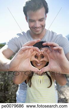 Stock image of portrait of father and daughter making heart shape with