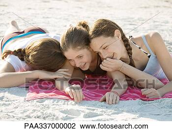 Three preteen girls lying on beach and giggling View Large Photo Image