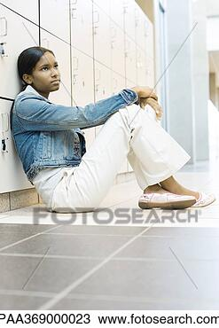Stock Photo - teenage girl sitting  on floor, leaning  against lockers.  fotosearch - search  stock photos,  pictures, wall  murals, images,  and photo clipart