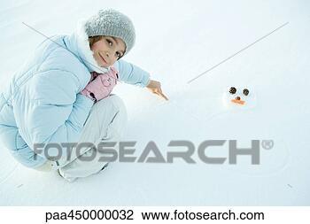 preteen, menina, crouching, em, neve, desenho, boneco neve, sorrindo ...