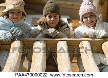 Three preteen or teen girls standing on deck of log cabin, looking ...
