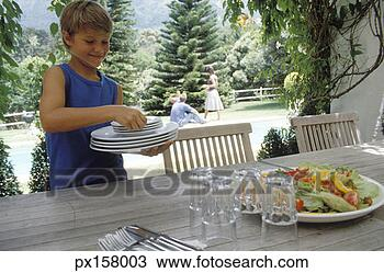Stock Photo - view of a young boy setting the table  fotosearch    Boy Setting The Table