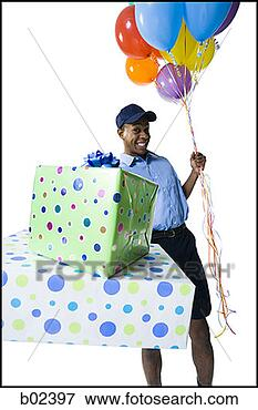Picture of Portrait of a delivery man holding gifts and balloons