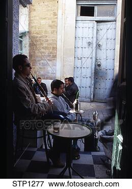Picture - north africa tunisia  men sat smoking  a chicha in the  medina in tunis.  fotosearch - search  stock photos,  pictures, images,  and photo clipart