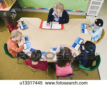 Stock Image - kindergarten students sitting at table with their teacher. fotosearch - search stock photos, pictures, wall murals, images, and photo clipart