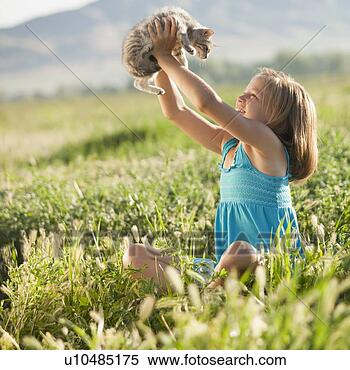 Stock Image - young girl holding  a kitten. fotosearch  - search stock  photos, pictures,  wall murals, images,  and photo clipart