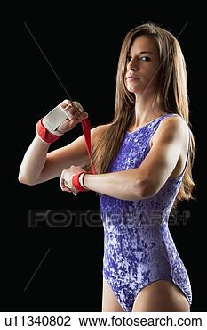 Stock Photo of Young Gymnast woman putting on hand grips u11340802 ...
