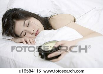 Banco de Imagem - jovem, mulher,  dormir, segurando,  alarme, relógio,  cama. fotosearch  - busca de fotos,  imagens e clipart