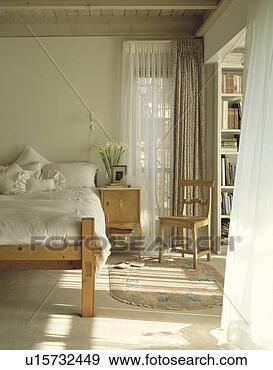 stock fotograf creme leinen auf kiefer bett in schalfzimmer mit blo wei vorh nge. Black Bedroom Furniture Sets. Home Design Ideas