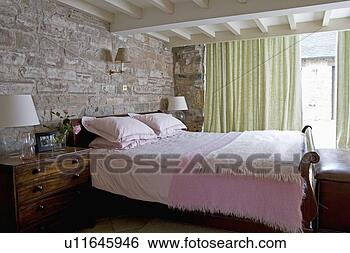 Stock afbeeldingen blootgestelde steenmuur achter bed met roze dekens in huisje - Pastel slaapkamer kind ...