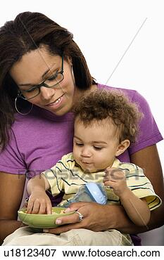 African American mid adult mom sitting with toddler son on lap eating ...