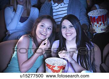 Arquivo de Fotografias - dois, jovem, mulheres,  compartilhar,  pipoca, cinema.  fotosearch - busca  de fotos, imagens  e clipart
