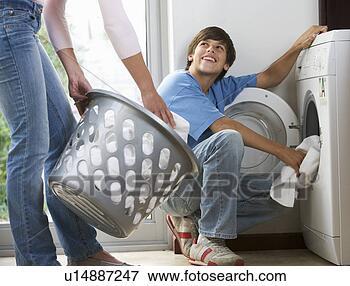 Foto - mãe, carregando,  lavando, máquina.  fotosearch - busca  de fotos, imagens  e clipart