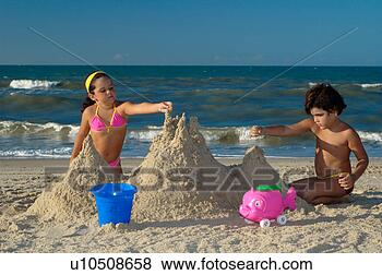 Children making a sand castle on the beach on a sunny day view large