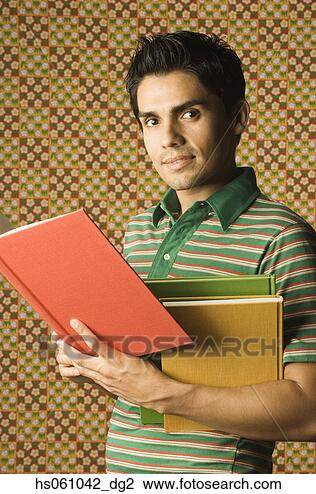 Stock Photo - young man holding  multicolored books.  fotosearch - search  stock photos,  pictures, wall  murals, images,  and photo clipart