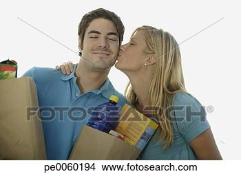 Stock Photo - couple outdoors  holding grocery  bags and kissing.  fotosearch - search  stock photos,  pictures, wall  murals, images,  and photo clipart