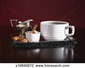Cup of coffee, pitcher of cream, raw sugar cubes and cookies on tray ...