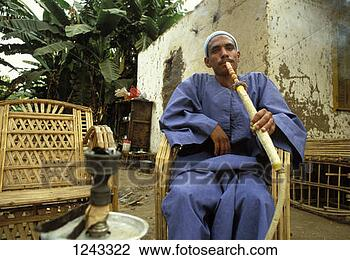 Stock Photo - a man smoking  a hookah location:  egypt. fotosearch  - search stock  photos, pictures,  images, and photo  clipart